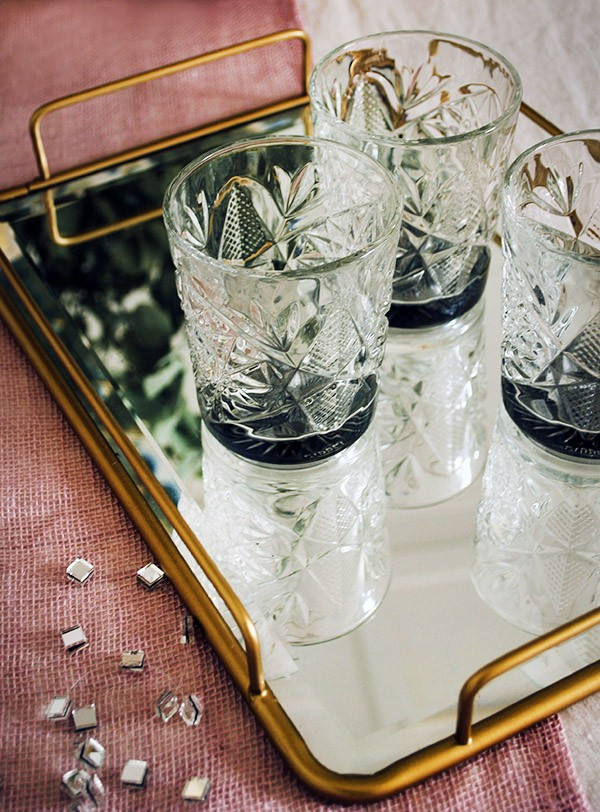 Serve your drinks on a mirror-topped tray for a dash of festive flair. West Elm's Fishs Eddy brass mirror topped tray.