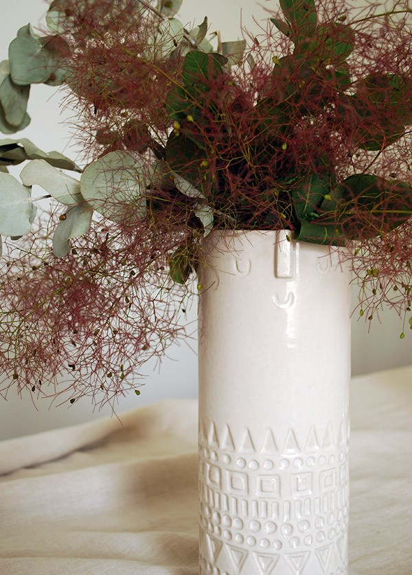 We created a beautiful centrepiece with a mid-century style vase. West Elm's Atelier Stella vase is perfect, and we filled it with dusky pink smoke bush and eucalyptus leaves.
