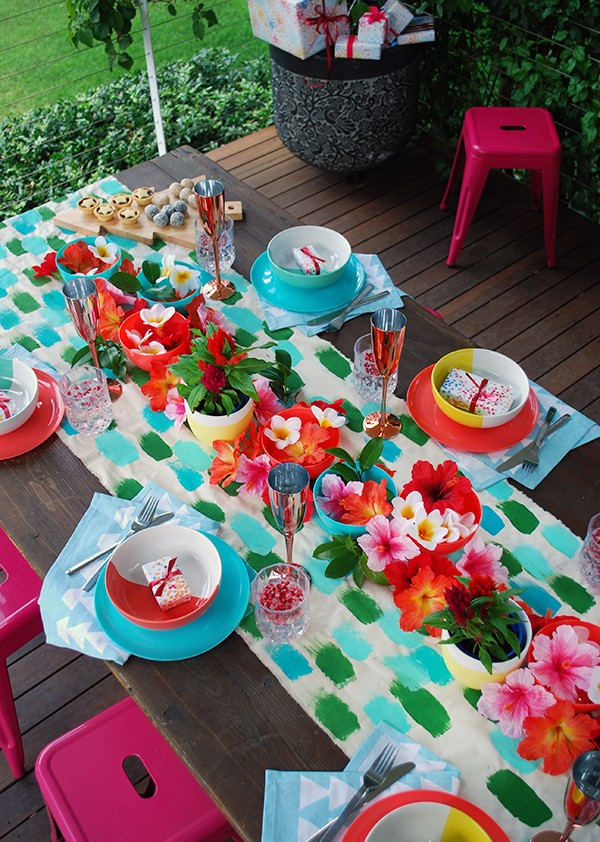 a tropical christmas table setting with a handpainted table runner adorned with hibiscus frangipani