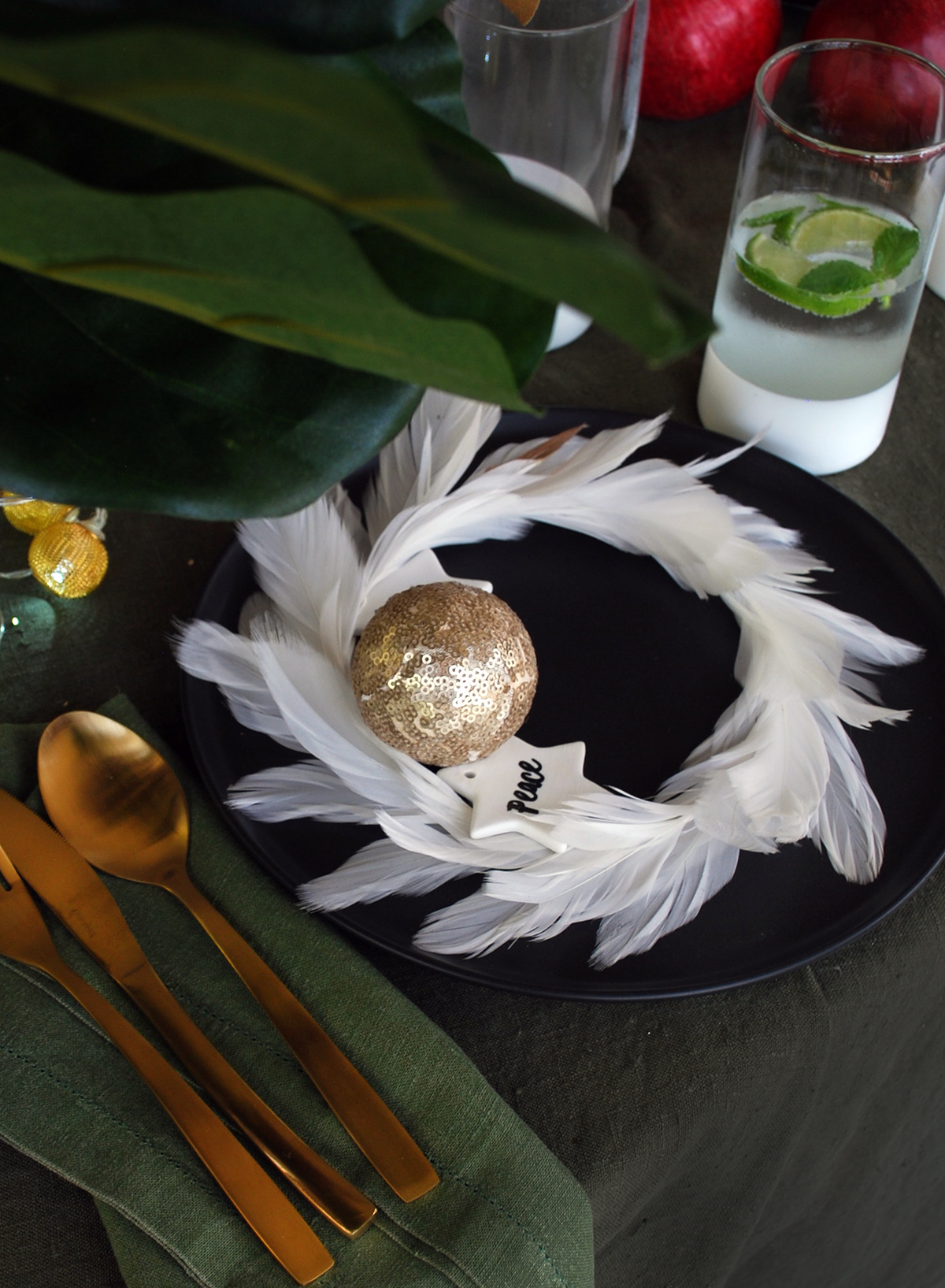 How to style a black Christmas table setting. Add texture and colour with this feather wreath as a place setting.