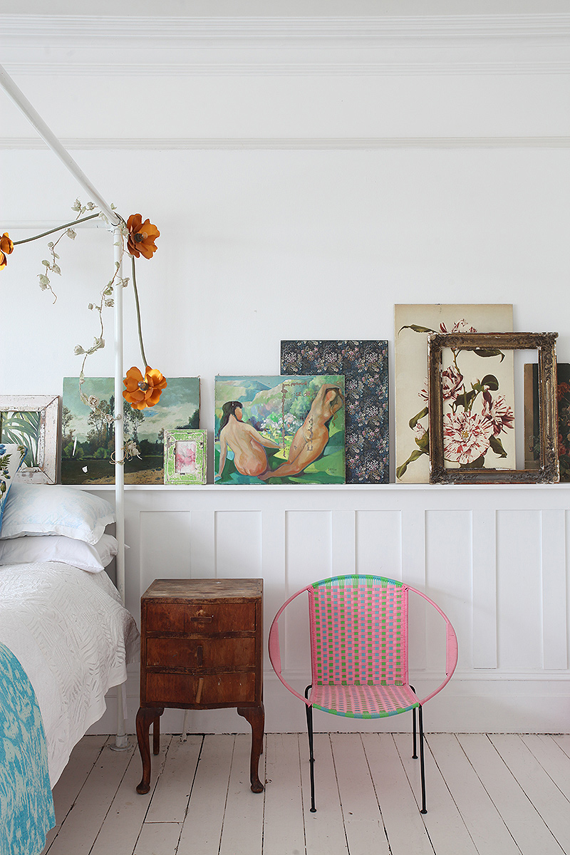An eclectic collection of paintings adds interest to the bedroom in this modern bohemian home